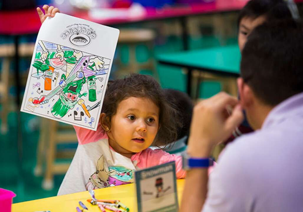 Sarah Chirih, 4, shows her coloring page to her father at the Crayola Experience, one of only two in the world. The other is in Easton, Pa.