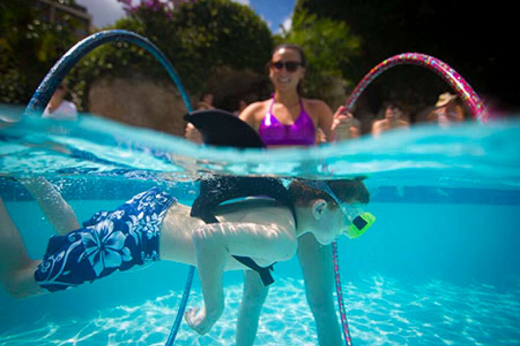 A young shark swims through hula hoops during The Mermaid Academy at the Hyatt Regency Grand Cypress in Orlando.