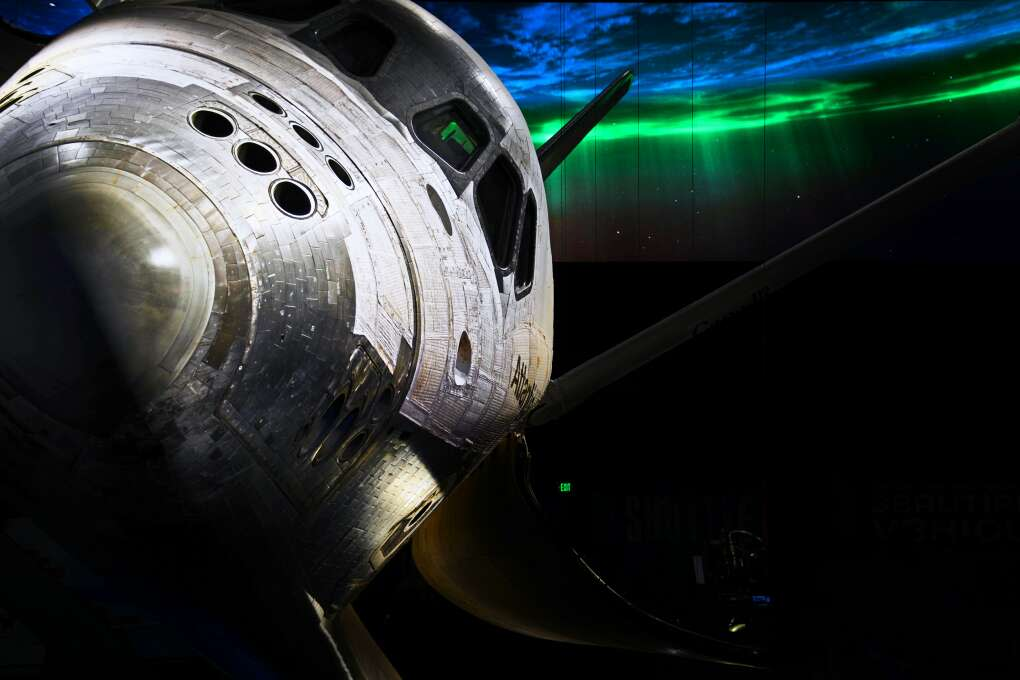 A film of a rotating Earth behind Space Shuttle Atlantis gives the appearance of the shuttle in orbit at the Kennedy Space Center Visitors Complex.