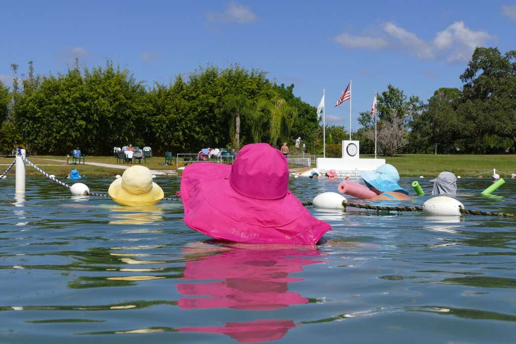 Visitors wear colorful hats as they float in the historic Warm Mineral Springs, North Port, FL.