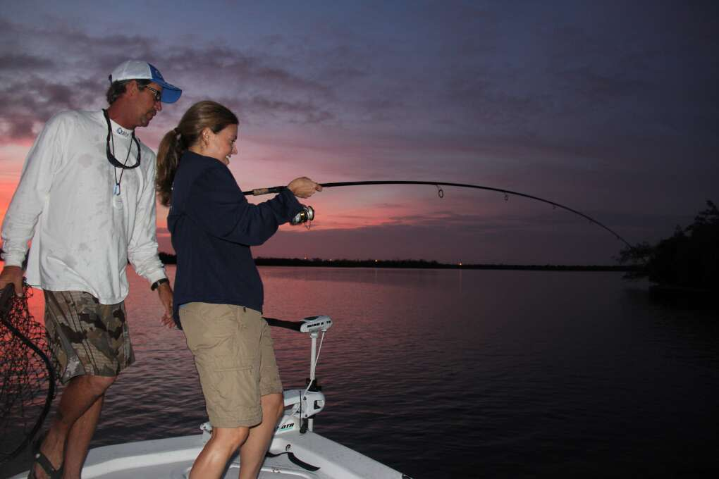 A guide coaches an enthusiastic angler hooked up on a big snook in the Indian River Lagoon.