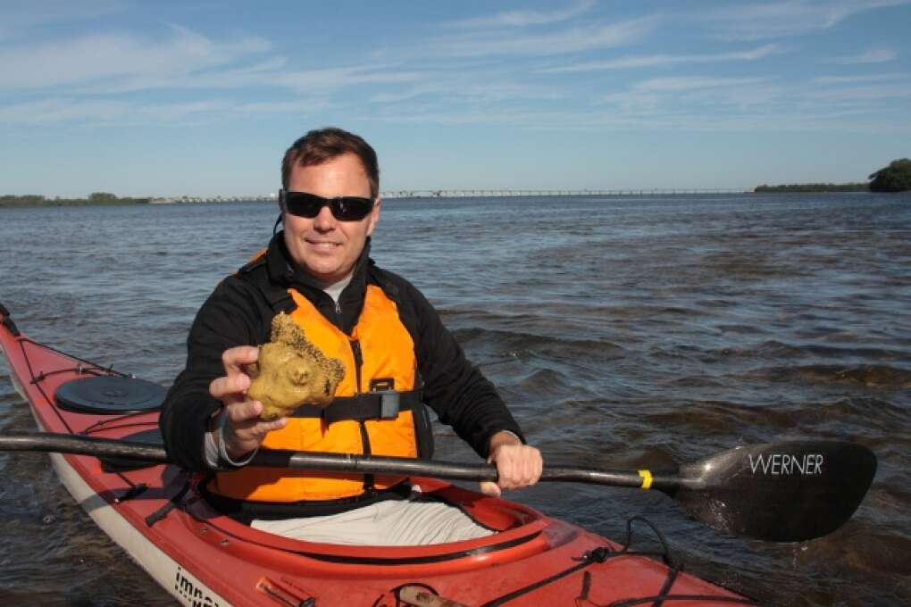 Man kayaking as he holds out a coral