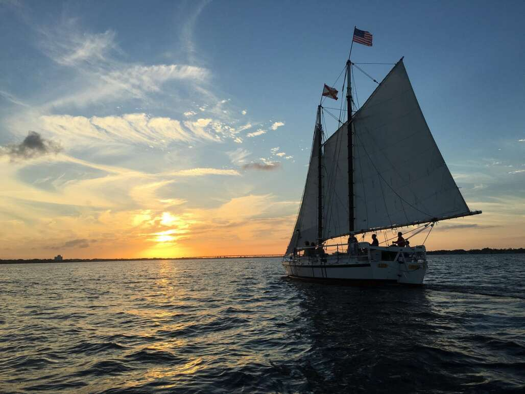 sailing boat on the ocean with a sunset in background