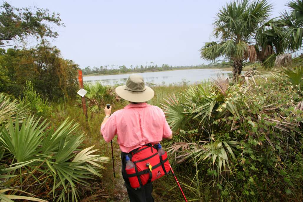 man hiking with a stick and a red bag at florida's state park