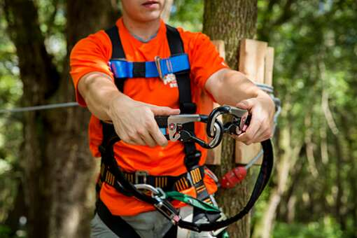 A staff member makes sure visitors know how their harness works before tackling the courses at TreeHoppers Aerial Adventure Park in Dade City.