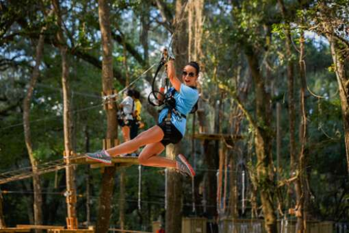 A member of Tampa Bay Moms blog enjoys her flight through the sky on a zipline at TreeHoppers Aerial Adventure Park in Dade City.