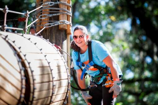 Jessica Cook of Tampa Bay Moms Blog (http://tampabay.citymomsblog.com) waits from another group member after completing an element at the TreeHoppers Aerial Adventure Park on September 20, 2015 in Dade City. VISIT FLORIDA/Scott Audette