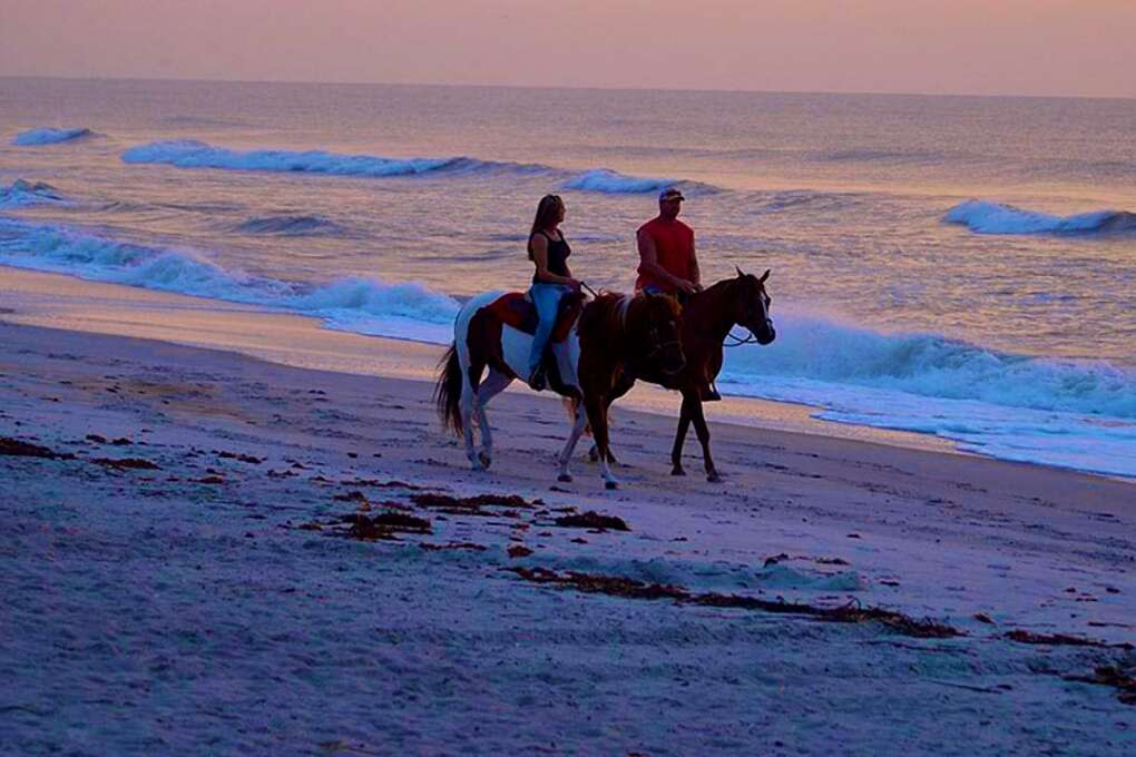 a couple riding horses by the beach