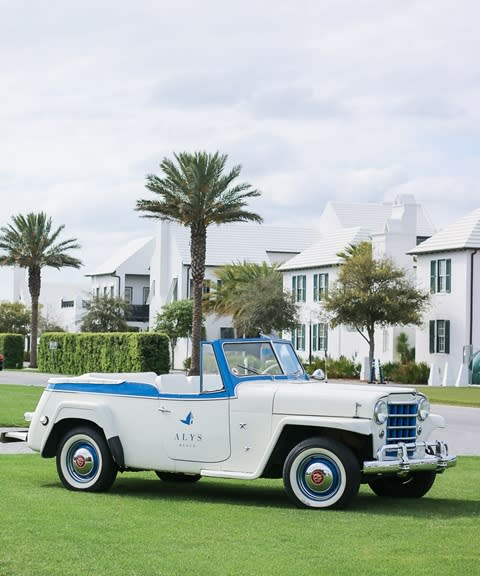 A white car parked by the beautiful green grass of the Alys Beach