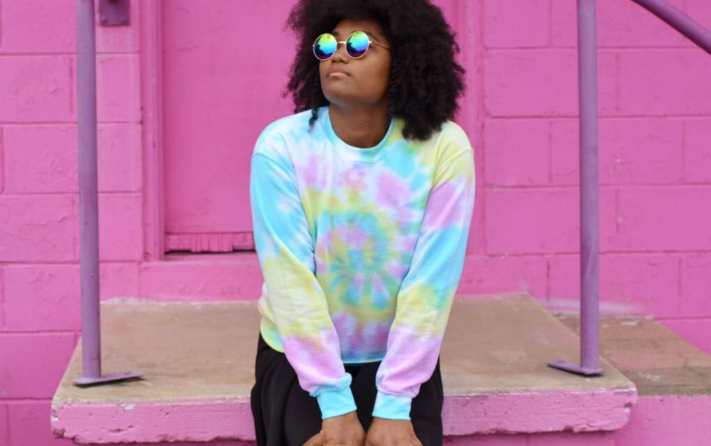 A Black womanl wearing sunglasses and colorful clothes with a pink wall in the background from The Fuzzy Pineapple, a black-owned business in Tallahassee, Fla.