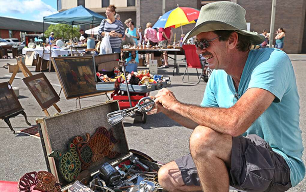 A man checks out an old egg beater in Arcadia's streets.
