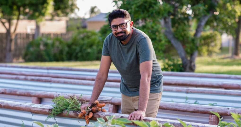 Chef Niven Patel Ghee in a garden with a bunch of carrots