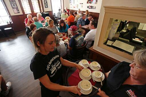 Server Bobbi Newberry, left, and manager Vicki Lowrey deliver cups of the famous clam chowder Tony's Seafood Restaurant. The recipe won a competition in Newport, R.I., three years running and was retired from competition.