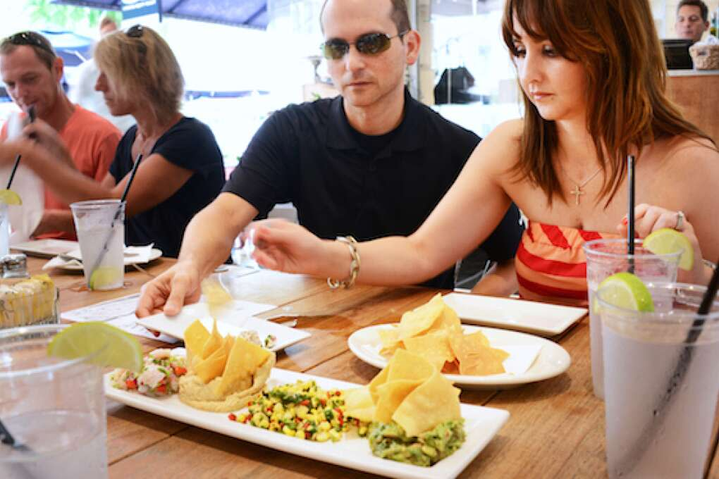 Mariela Rexach and Jose Rodriguez, visiting from Puerto Rico, enjoy  a plate of appetizers: hummus, corn salad, guacamole, ceviche and homemade corn chips, at Books & Books in Miami Beach.
