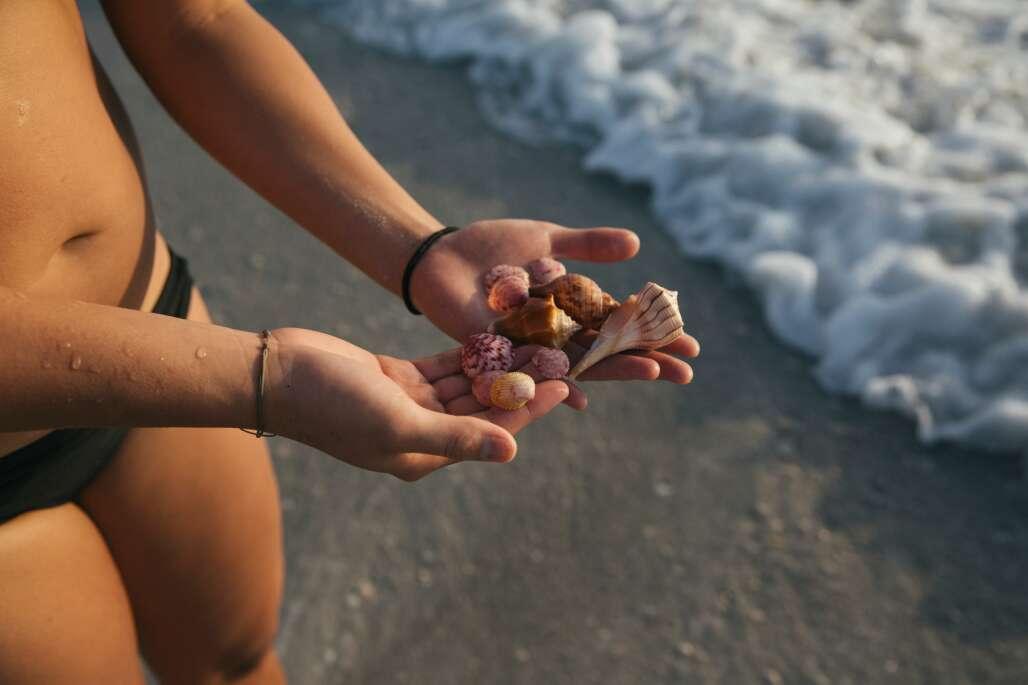girl holding handful of shells on beach