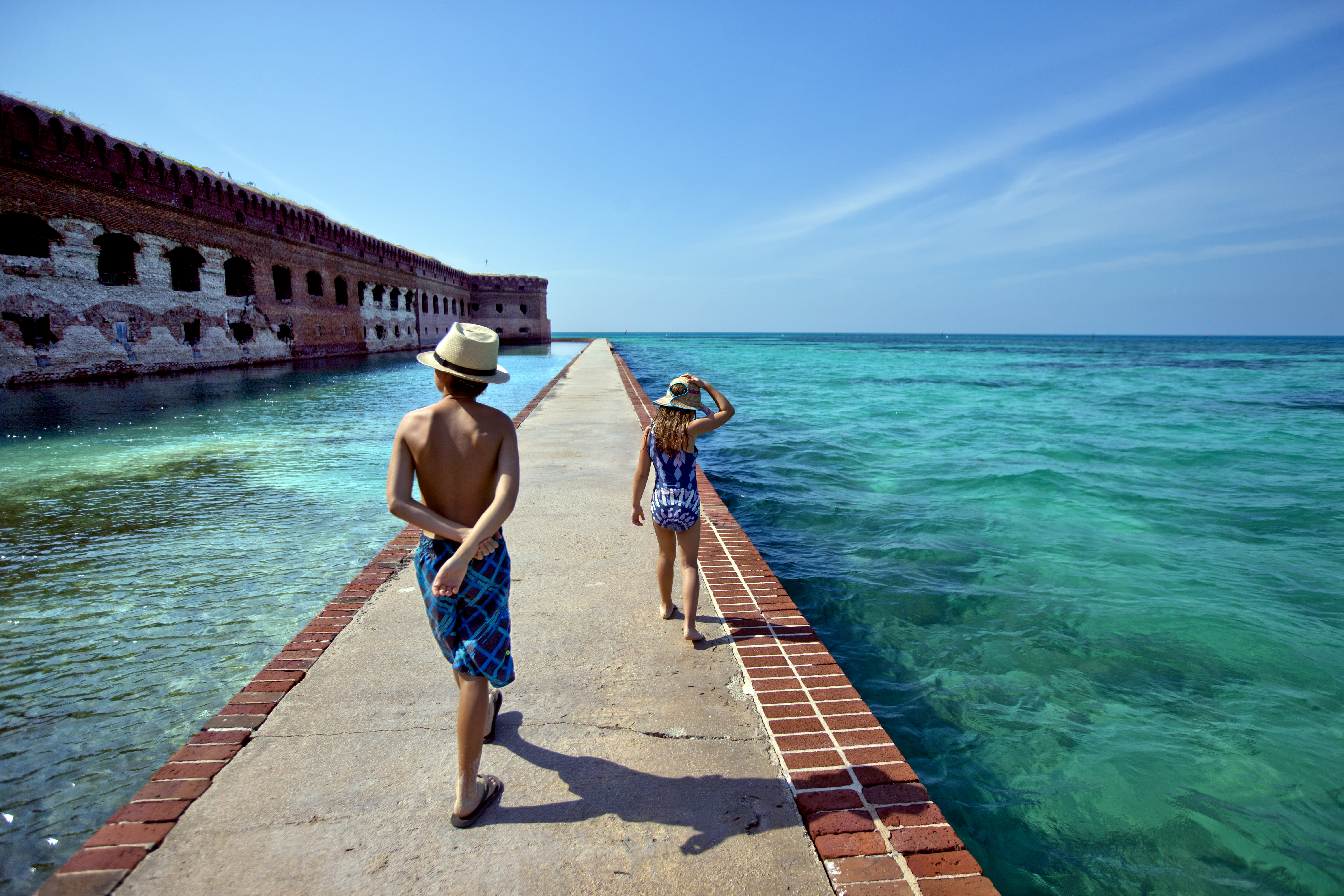 Two children walking down a path surrounded by water at Fort Jefferson in Dry Tortugas National Park