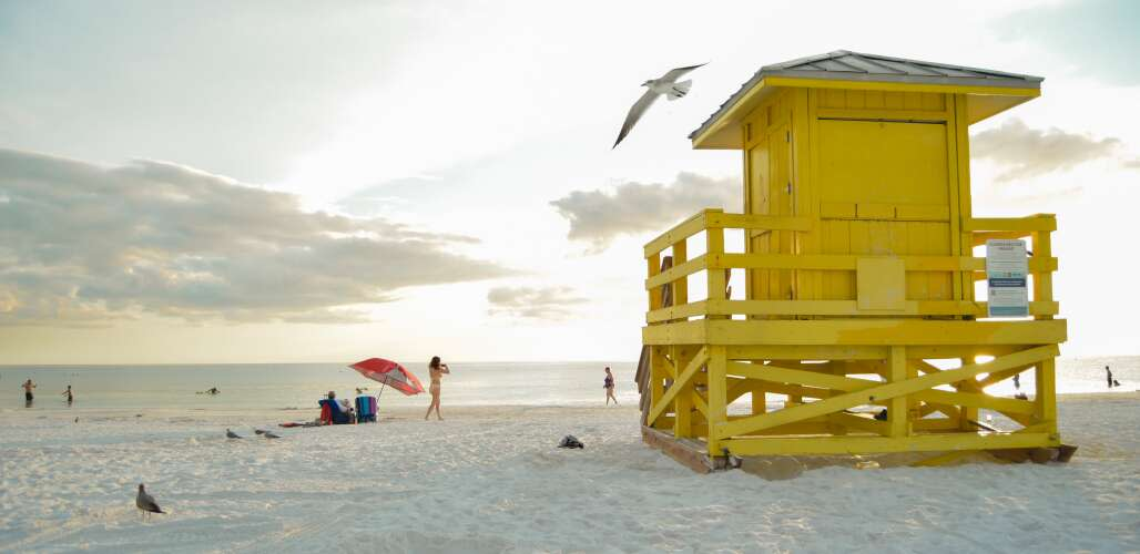 a yellow lifeguard post surrounded by visitors facing the sunset at siesta key beach in sarasota county