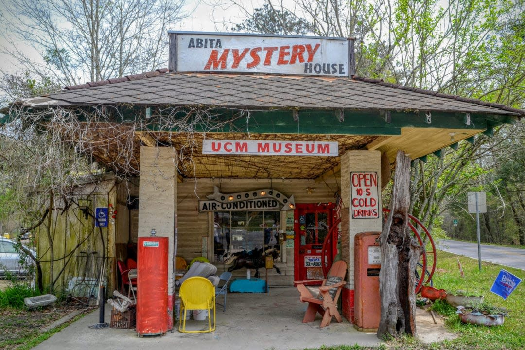 a converted gas station covered in handpainted signs and vintage goods