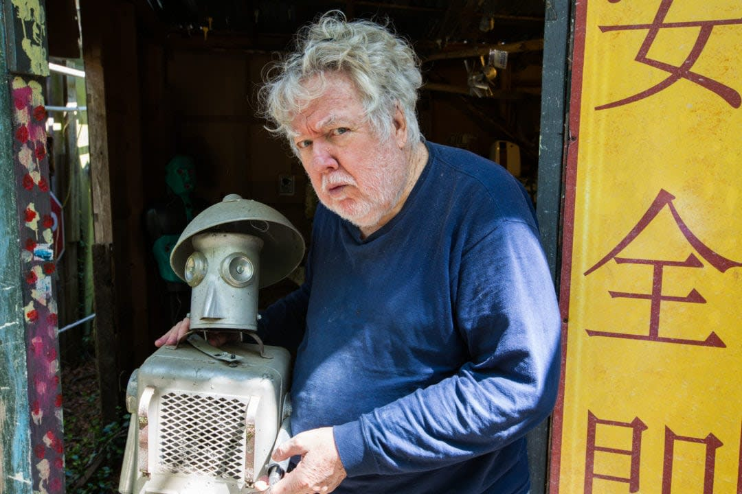 a white man with curly gray hair poses with a metal robot