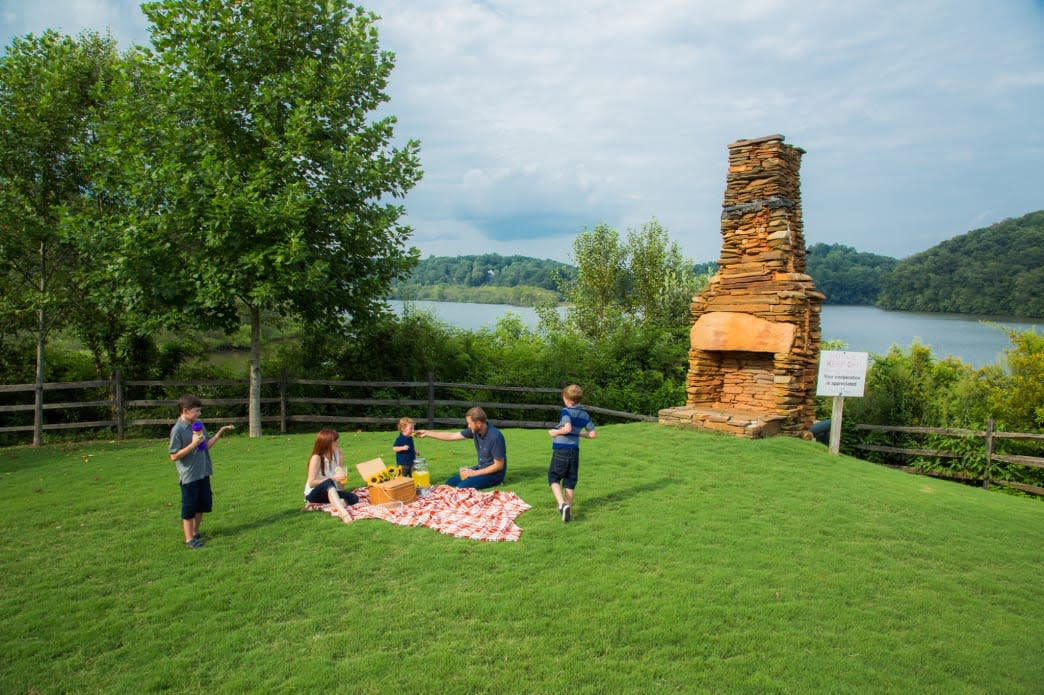 A family enjoys a picnic lunch in the grass at Morgan Falls Overlook Park