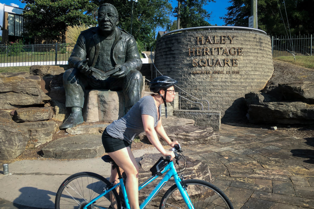 A biker zips past a statue of author Alex Haley in Knoxville's Morningside Park. 