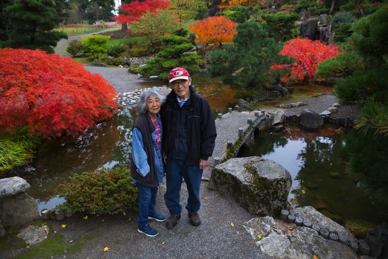 "Kiyoshi ""Hal"" Seike and his wife, Fukuye ""Fran"" Seike, stand in their Japanese garden in SeaTac, where they still work a few hours every Thursday. The Seike Japanese Garden was commissioned by Hal's father, an immigrant, partly as a tribute to his son Toll.  (Ellen M. Banner/The Seattle Times)"
