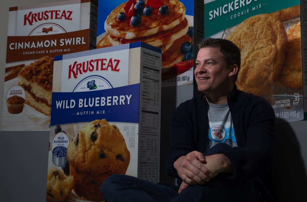 Andy Heily, CEO of Continental Mills (which makes Krusteaz food items), sits near boxes of items produced at the company's Tukwila headquarters last month. Seattle's Krusteaz started in the early 1930s and has been operated by the Heily family for three generations. (Ellen M. Banner / The Seattle Times)