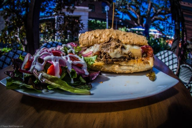 A Cuban sandwich with a side salad is served outside under the oaks at Mosaic in Ocean Springs, Miss.
