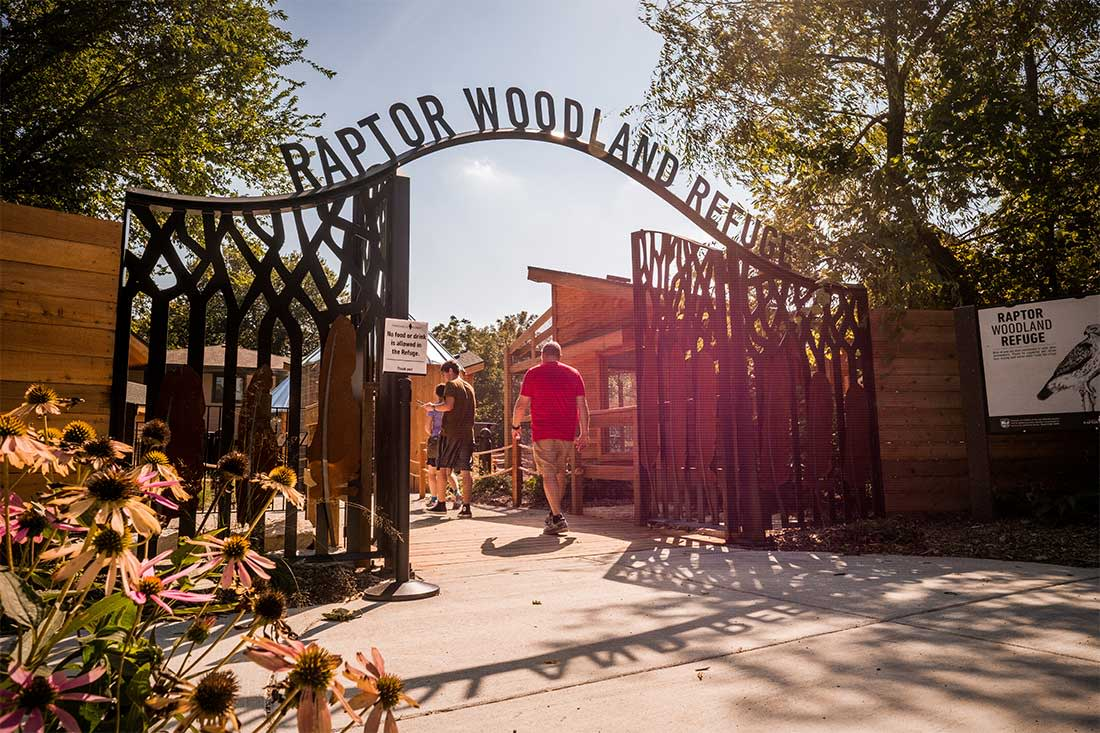 A decorative gate with sign welcomes visitors to the Raptor Woodland Refuge at Fontenelle Forest near Omaha, Nebraska