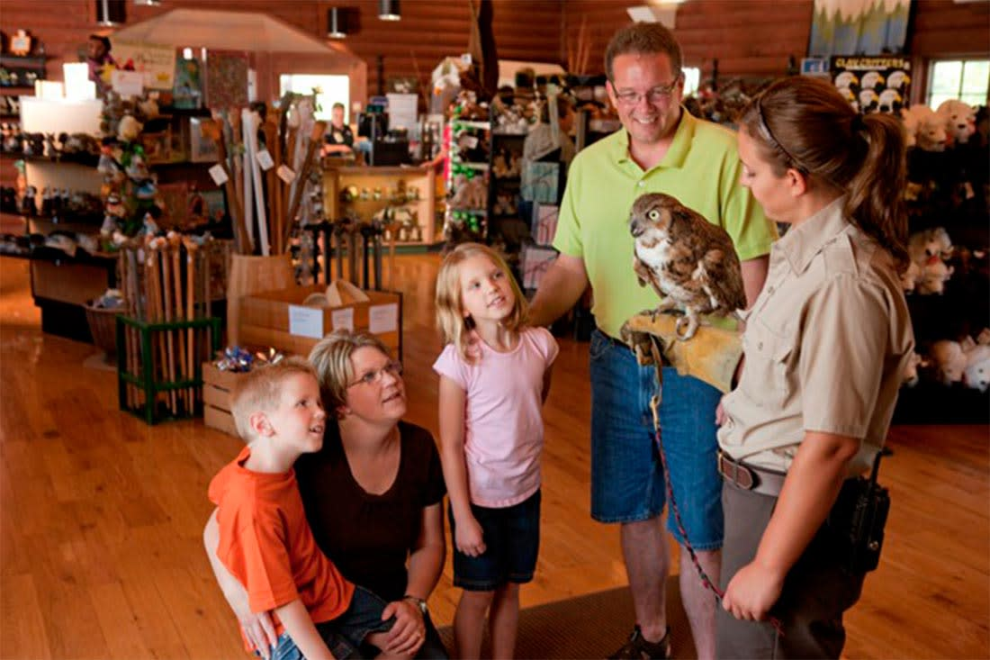 A family with two children gather around a raptor at the Lee G. Simmons Conservation Park & Wildlife Safari near Omaha, Nebraska