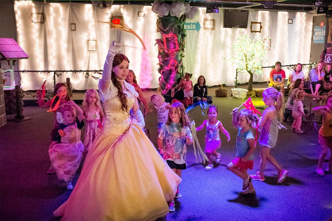A woman dressed as a princess leads a group of girls in a parade at the Omaha Children's Museum in Omaha, Nebraska