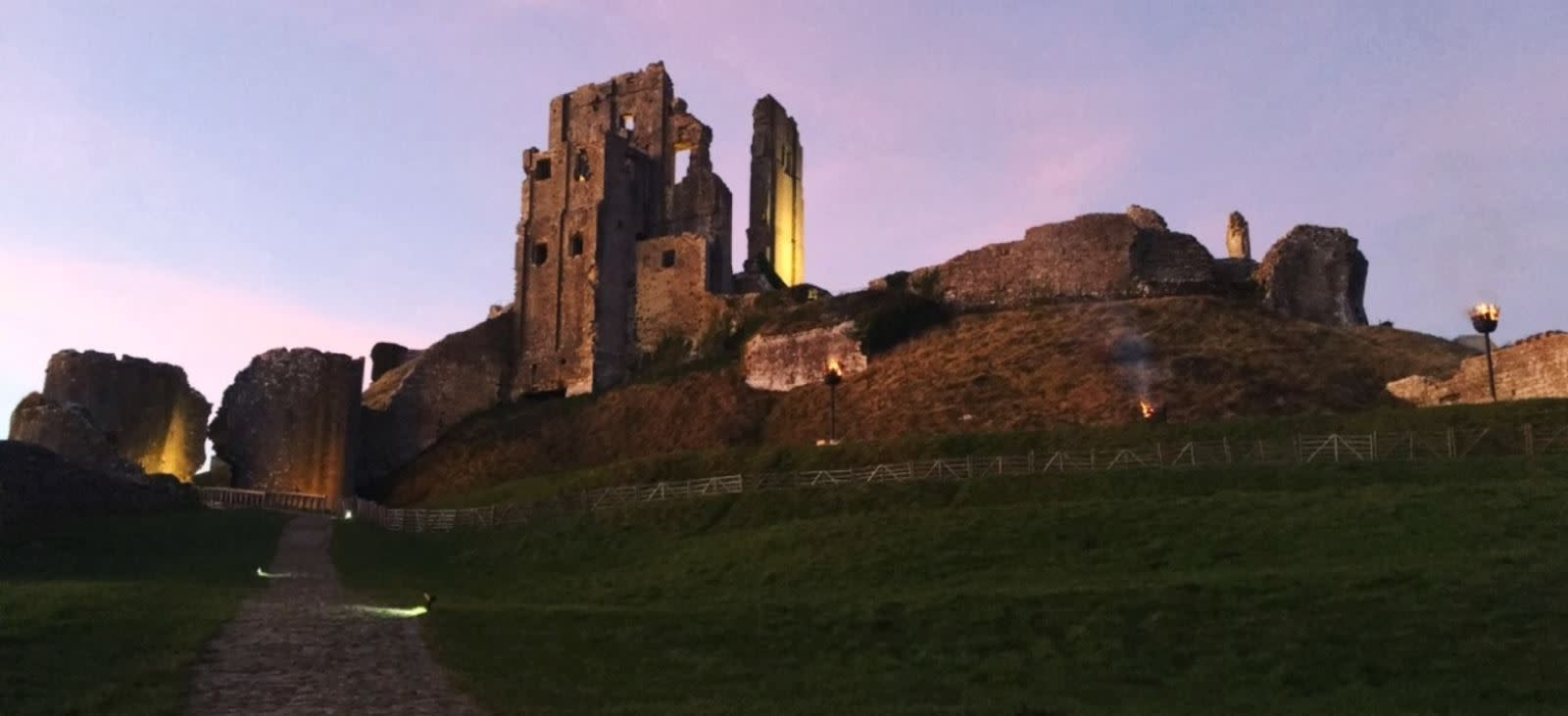 A pink sky blooms as the sun sets behind the romantic ruins of Corfe Castle
