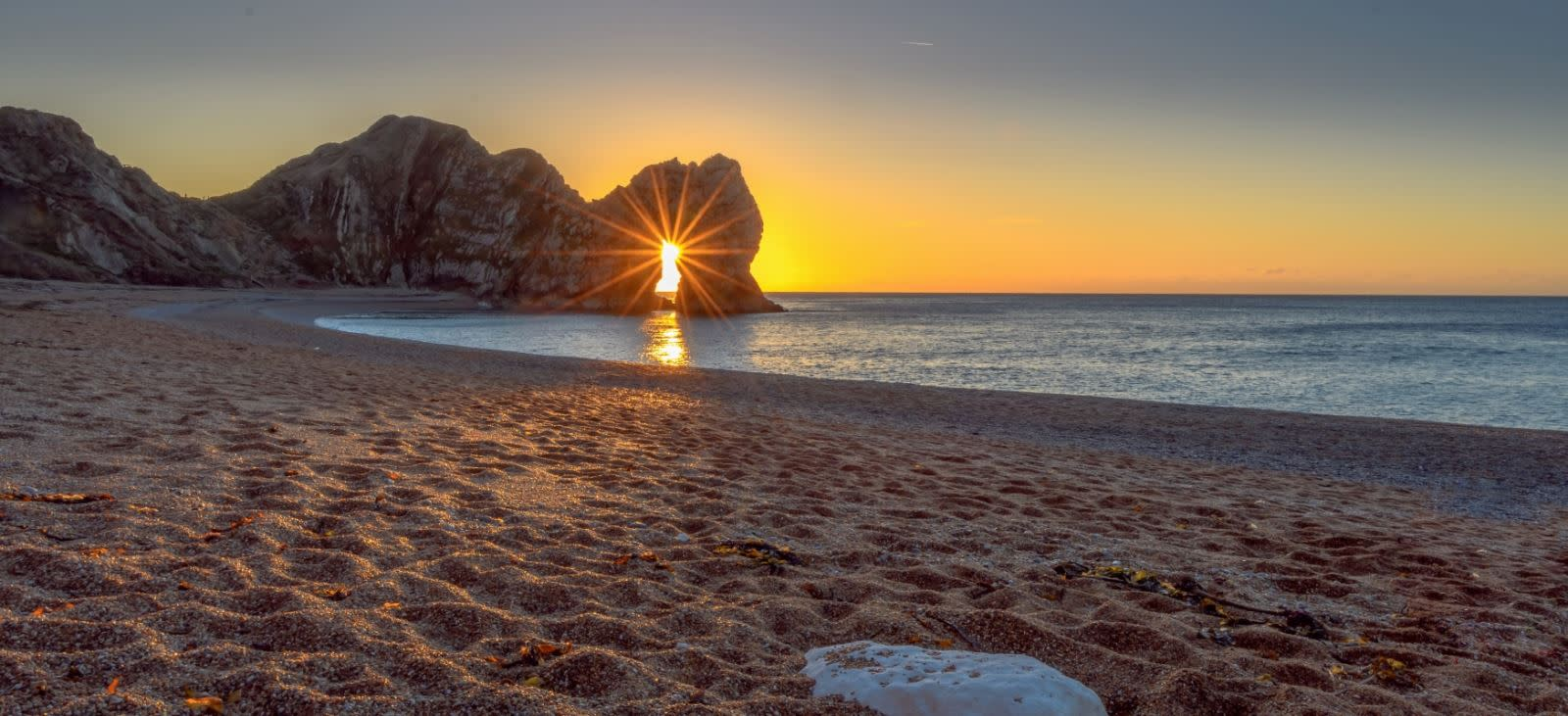 A glorious sight of the sun rising through the arc of Durdle Door