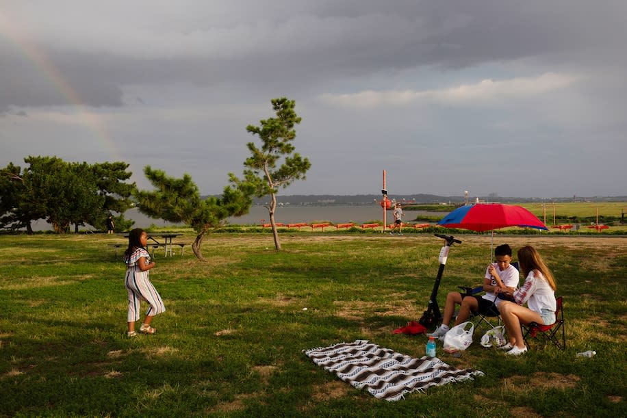 A rainbow appears shortly after the rain as people at Gravelly Point Park in Arlington, Va., wait to watch planes take off from Reagan National Airport.