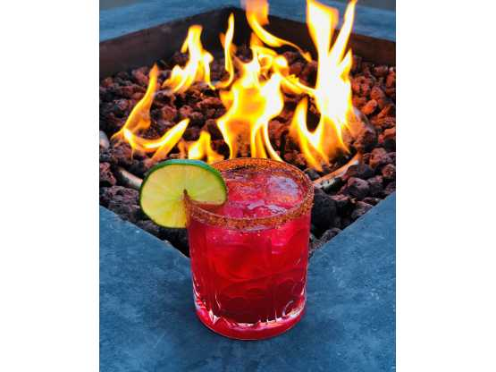 Tatu red drink in front of fire