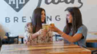 Two women cheers their beers and smile inside the tasting room of Mirror Twin Brewing.