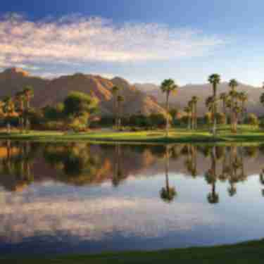 Beautiful lake at Indian Wells Golf Resort with the mountains, palm trees and green grass.