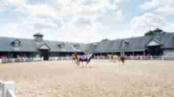 Four horseback riders canter in a circle inside a fenced off field at Kentucky Horse Park.
