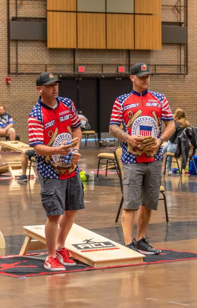 Two men throwing cornhole bags in tournament