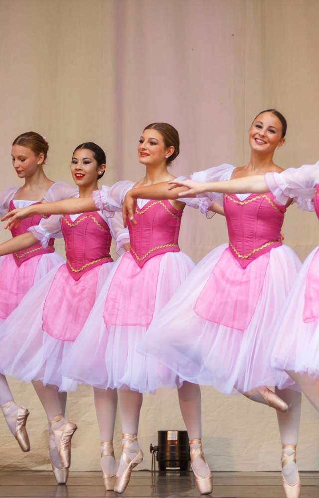 5 ballerinas dance on a stage