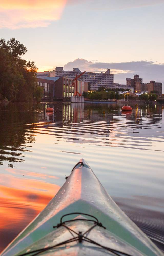 A kayak in the St. Joseph River with the Century Center in the background
