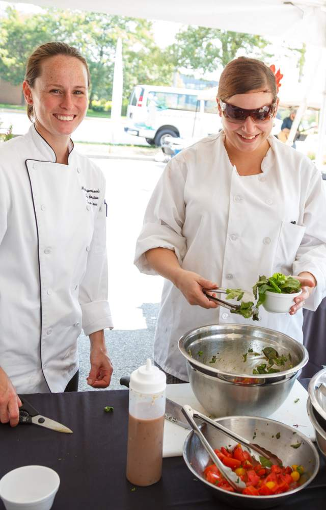 Two chefs prepare food at an outside venue in South Bend