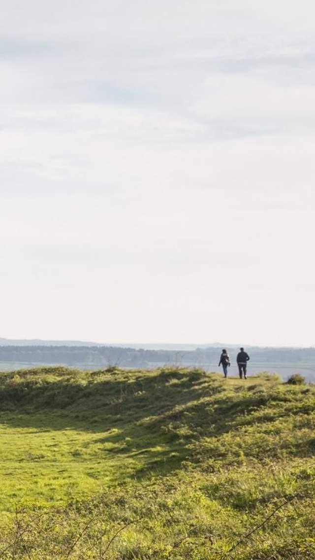 Two people walking at Badbury Rings.