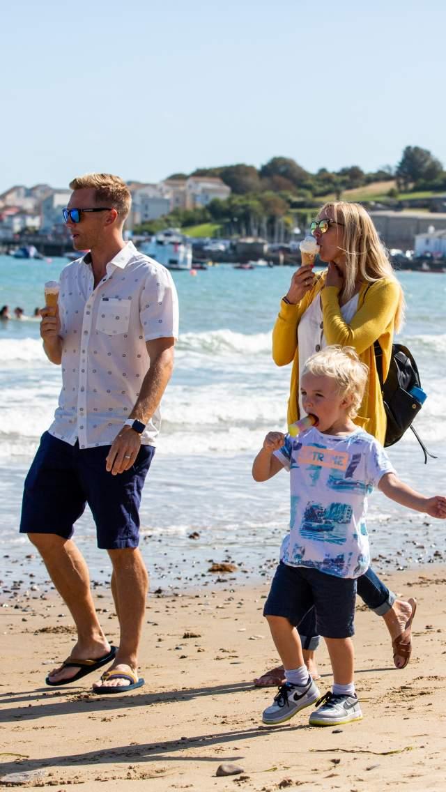 Family enjoying ice creams walking along Swanage Beach