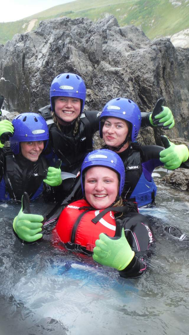 A group of 6 people coasteering with Cumulus Outdoor Adventure