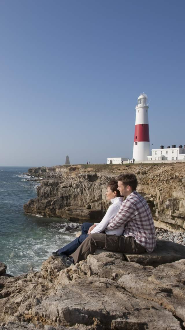 Man and woman sitting on the rocks at Portland Bill, Dorset