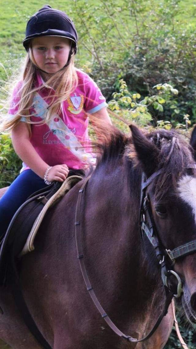 Little girl riding a horse with a lady guiding the horse