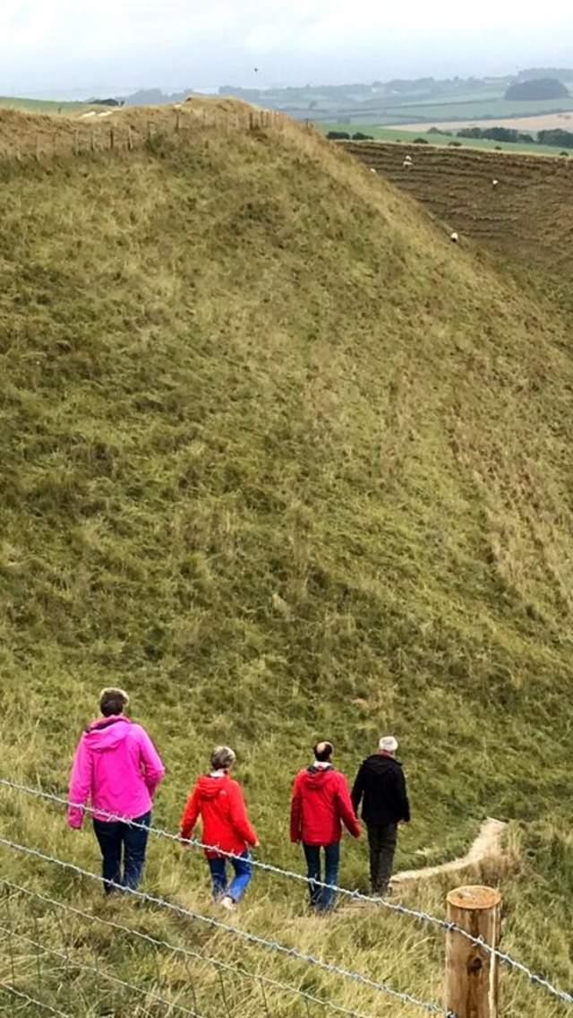 Four people walking Maiden Castle