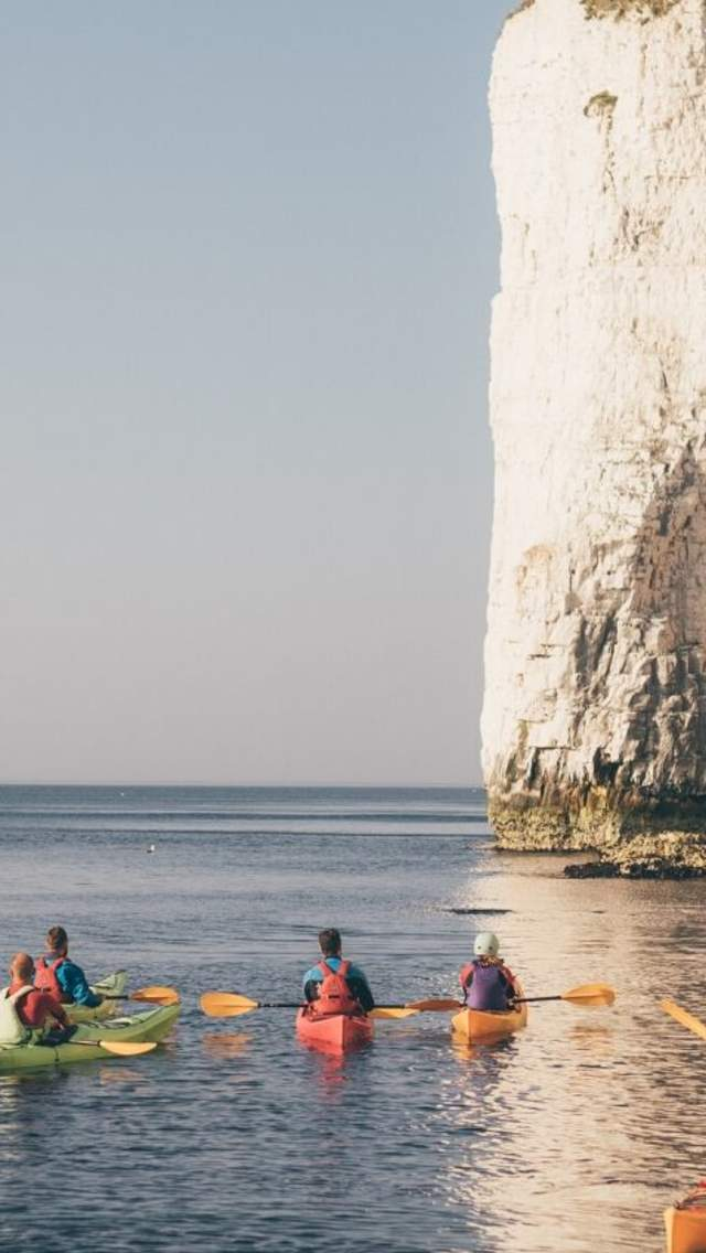 A group of canoes at the base of Old Harry Rocks