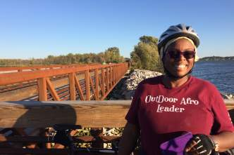 A woman smiles in front of the Lower Yahara Trail bridge